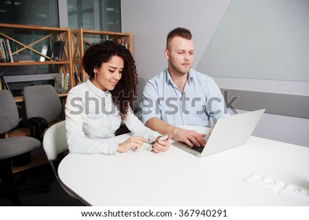 Two Serious Young Business People Sitting at the Table with Laptop and Documents, Busy with Their Respective Mobile Phones - stock photo