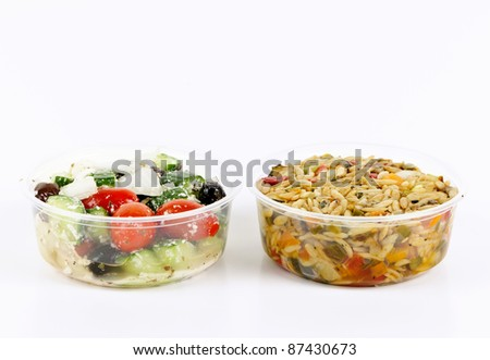Two servings of prepared salad in plastic takeaway containers - stock photo