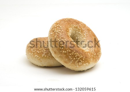 Two sesame seed bagels on a white background - stock photo