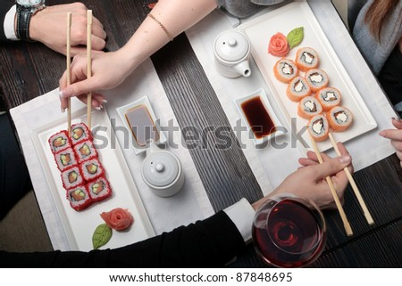 Two sets of California maki sushi roll on white plates elegantly decorated, a woman eating maki with chopsticks on a background - stock photo