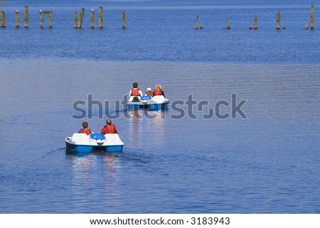 Two sets of daytrippers in pedalos on Loch Lomond, Scotland. - stock photo