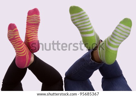 Two sets of girls feet wearing striped socks with legs crossed - stock photo