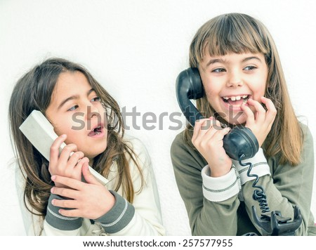 Two seven year old girls talking on the old vintage phones with the white background - stock photo