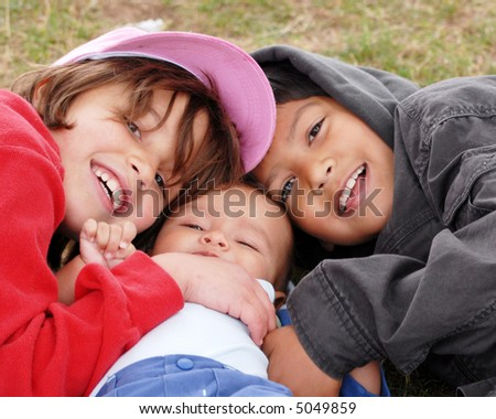 Two seven-year-olds cuddling with an infant on the grass. - stock photo
