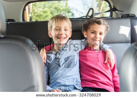 Two seven years old are sitting at the back of a car They are looking at camera, smiling arms in arms like friends or brother and sister The blond boy is wearing a blue shirt and the girl a pink top