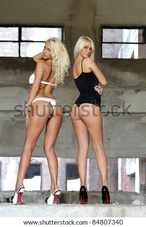 Two sexy ass woman in ruins at sunset .Erotic art photo. - stock photo
