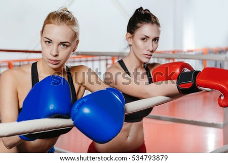 Two sexy athletic girls leaning on the ropes