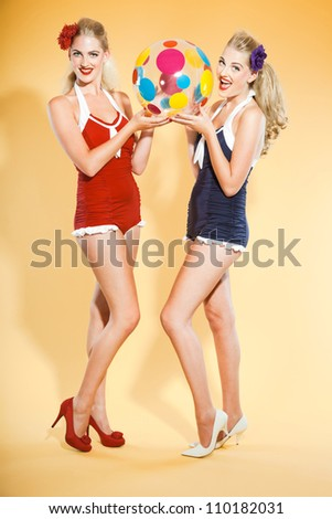 Two sexy blond pin up girls wearing blue and red swimwear holding a colorful beach ball. Retro style. Fashion studio shot isolated on yellow background. - stock photo