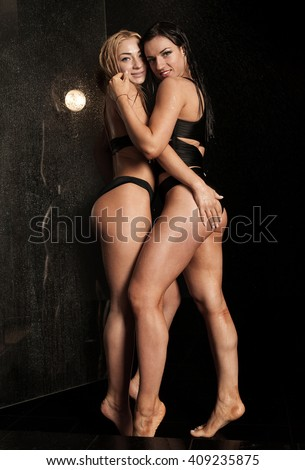 two sexy brunette and blond models women standing against a wall in a black bikini on black background in water studio. Water drops on woman body. - stock photo