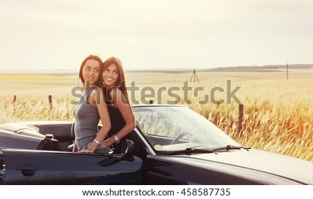 Two sexy brunette woman standing near her car on the road in pitch and photographed.
