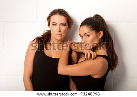 Two Sexy Brunettes In Leotards with the one woman leaning on the shoulder of the second in an intimate friendly gesture - stock photo