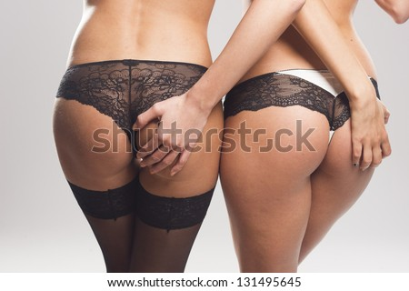 Two sexy female asses in lingerie on gray isolated - stock photo