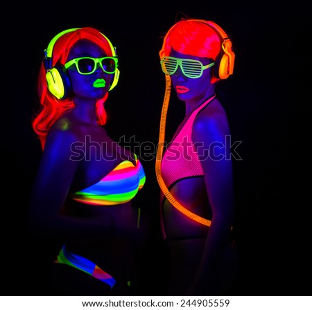 two sexy female disco dancers posing in UV costume - stock photo