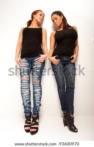Two sexy female friends dressed casually in jeans posing full length in the studio on white. - stock photo