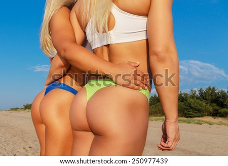 Two sexy female in swimwear standing on the beach under blue sky. Rear view. - stock photo