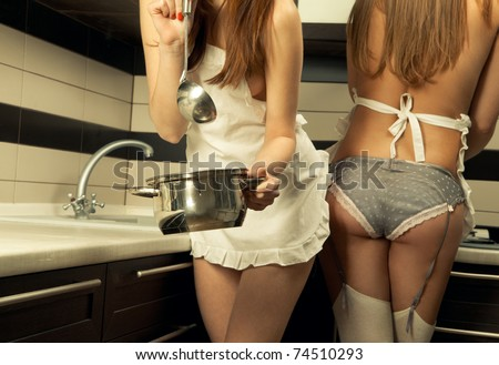 Two sexy housewifes in kitchen room - stock photo