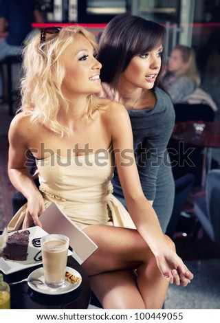 Two sexy ladies in a cafe - stock photo