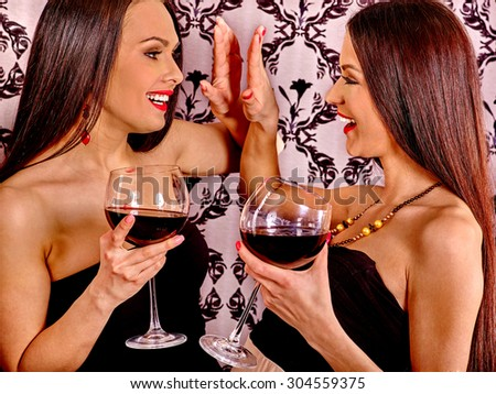 Two sexy lesbian women with red wine.Black background.
