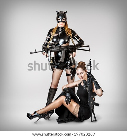 Two sexy models holding automatics on gray background in studio - stock photo