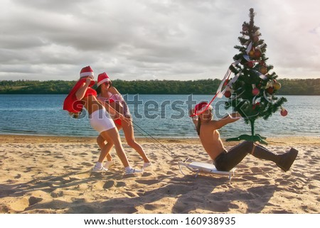 Two Sexy Santos  pulling Santa on a sled with Christmas tree at the beach.  (concept: Tropical winter fun) - stock photo