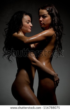 Two sexy woman kissing in darkness - stock photo