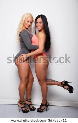 Two sexy womans in underwear posing over white wall. - stock photo