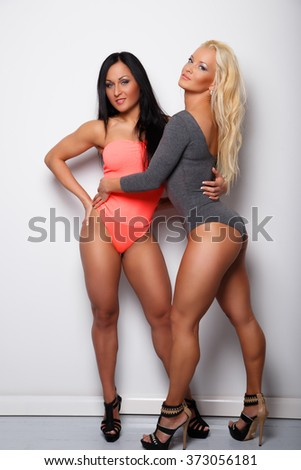 Two sexy women in underwear posing over light wall. - stock photo