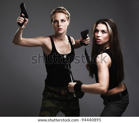 two sexy women with gun and dagger on gray - stock photo