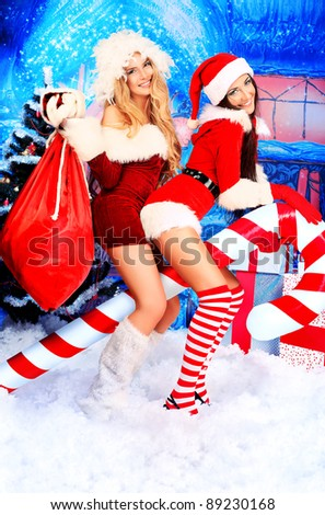 Two sexy young women in Christmas clothes posing over Christmas background. - stock photo