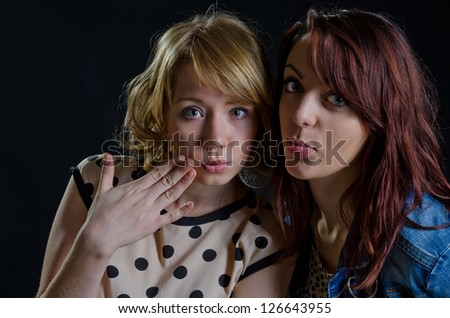 Two sexy young women posing with their heads close together pouting their lips in a seductive manner - stock photo