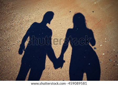 two shadows holding hands on a beach