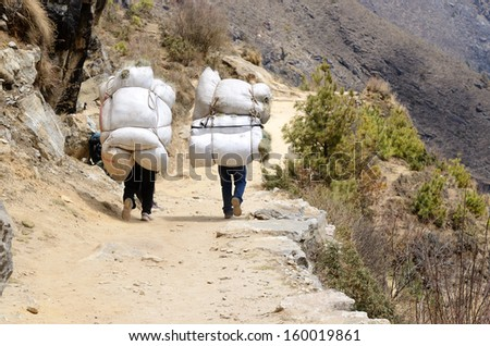 Two sherpa porters carrying heavy sacks in the Himalayas at Everest Base Camp trek ,Nepal.Sherpas are elite mountaineers and experts in the Himalaya mountains.  - stock photo