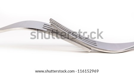 Two shiny forks together on white surface