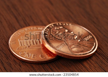Two shiny new pennies on wood background.  Macro with extremely shallow dof.  Concept - two cents worth.