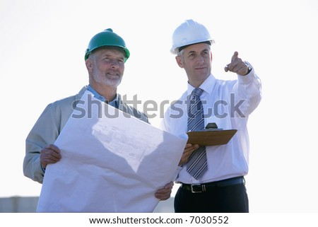 Two shipping engineers studying plans and pointing - stock photo
