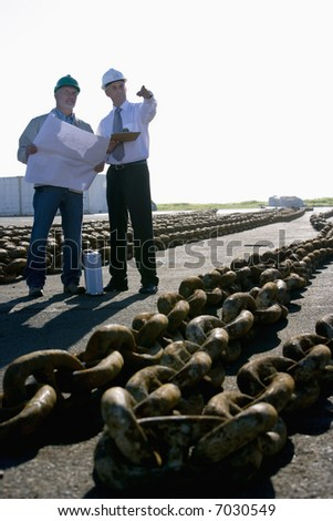 Two shipping engineers studying plans whilst standing with large anchor chains in the harbor - stock photo