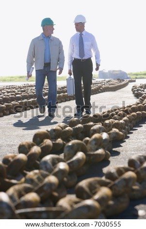 Two shipping engineers walking amongst large anchor chains in the harbor - stock photo