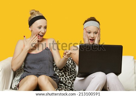 Two shocked young women using laptop sitting on sofa against yellow background - stock photo