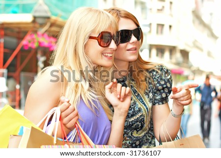 Two shopping woman looking away with  bags in city environment.