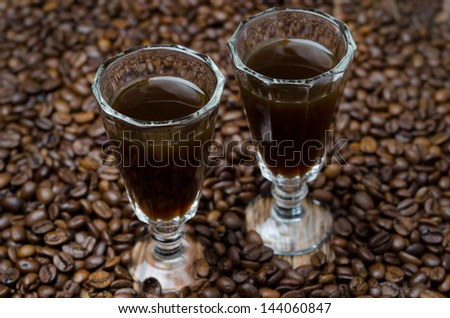 two shot glasses of coffee liqueur on the background of coffee beans, selective focus