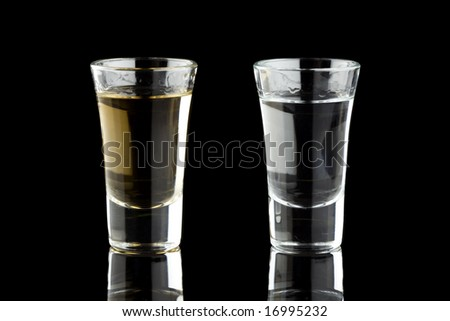Two shots of tequila isolated on a black background - stock photo