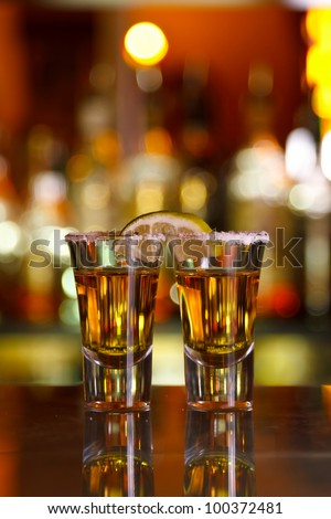 two shots of tequila with lime and salt on the bar on the background of the bar - stock photo