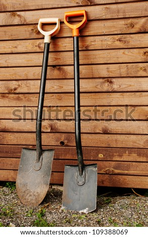 Two shovels against wooden wall - stock photo