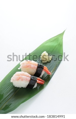 Two shrimp sushi rolls sitting on a green leaf. - stock photo