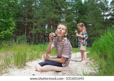 Two sibling children are playing with soap bubbles on sand dune beach at pinewood background - stock photo