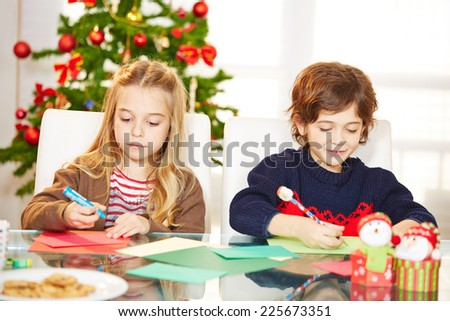 Two siblings drawing cards at christmas with handicrafts - stock photo