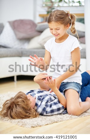 Two siblings fighting in fun at home in the living room - stock photo