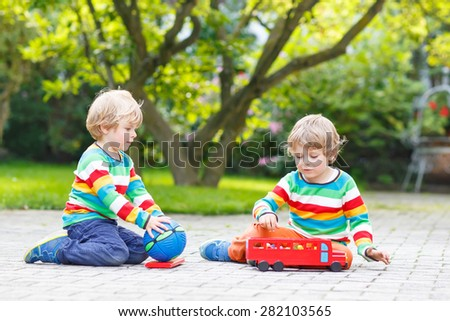 Two siblings, kid boys in colorful clothing with stripes playing with red school bus and toys in summer garden on warm sunny day. Learning to play and communicate together. - stock photo