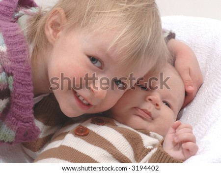 Two siblings - older sister and baby brother - both in striped sweaters - stock photo