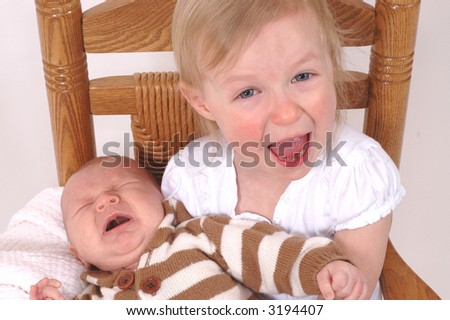 Two siblings - older sister and baby brother - having concurrent meltdowns - stock photo